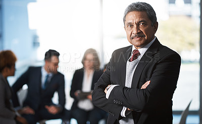 Buy stock photo Cropped portrait of a handsome mature businessman standing with his arms folded with his colleagues in the background