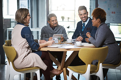 Buy stock photo Cropped shot of a group of businesspeople sitting in the boardroom during a meeting