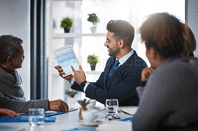 Buy stock photo Cropped shot of a handsome young businessman showing his colleagues something on a tablet during a meeting in the boardroom