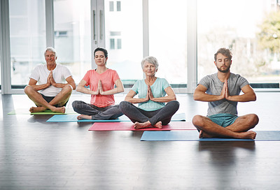 Buy stock photo Full length shot of a group of people meditating while practicing yoga