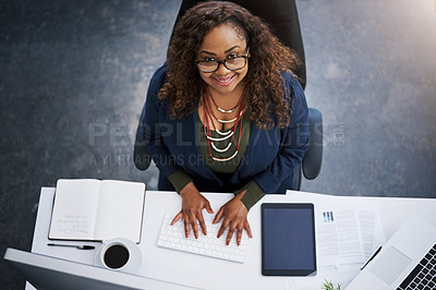 Buy stock photo High angle shot of a young businesswoman using a computer at her desk in a modern office