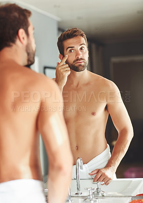 Buy stock photo Cropped shot of a shirtless young man checking out his eye in the bathroom mirror
