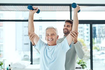 Buy stock photo Shot of a friendly physiotherapist helping his senior patient work out with weights