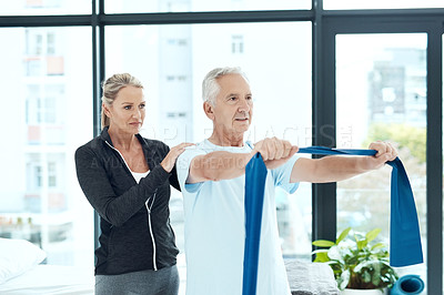 Buy stock photo Shot of a a physiotherapist working with a senior patient using a resistance band