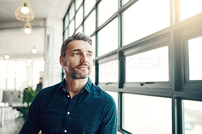 Buy stock photo Shot of a mature businessman looking thoughtfully out of an office window