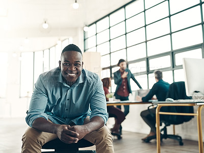 Buy stock photo Portrait of a young businessman sitting in a modern office with his colleagues working in the background