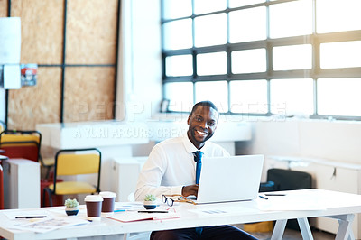 Buy stock photo Portrait of a focused young businessman typing on his laptop while being seated at his desk in the office at work during the day