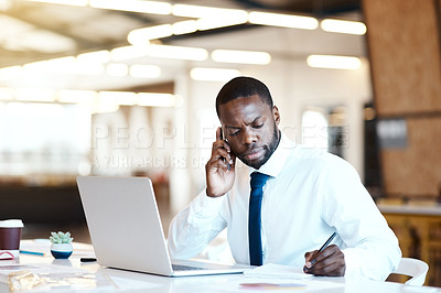 Buy stock photo Shot of a focused young businessman talking on his cellphone and making notes while being seated at his desk in the office during the day