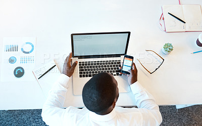 Buy stock photo High angle shot of an unrecognizable young businessman working on his laptop and checking his cellphone while being seated in the office