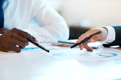 Buy stock photo Closeup of two unrecognizable businesspeople making notes while looking at graphs in the office at work during the day