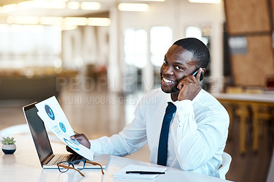 Buy stock photo Portrait of a cheerful young businessman talking on his cellphone and making notes while being seated at his desk in the office during the day