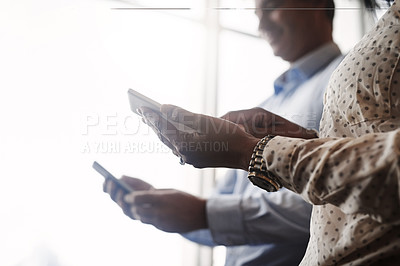 Buy stock photo Closeup shot of two unrecognisable businesspeople using digital devices in an office
