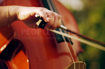 Buy stock photo Cropped shot of an unrecognizable woman playing a cello in the backyard
