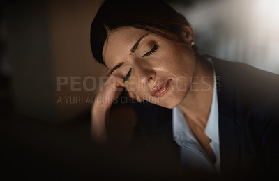 Buy stock photo Shot of a young businesswoman falling asleep at her desk during a late night in a modern office