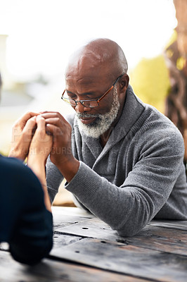 Buy stock photo Cropped shot of a senior couple holding hands in prayer while sitting outside