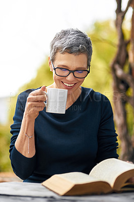 Buy stock photo Cropped shot of an attractive senior woman reading her bible while drinking coffee outside