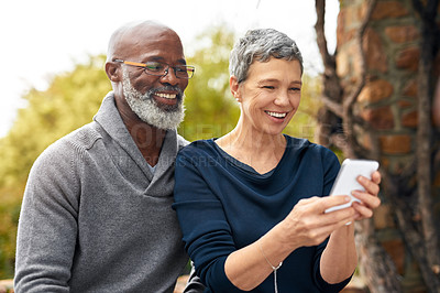 Buy stock photo Cropped shot of an affectionate senior couple using a cellphone while sitting in the park