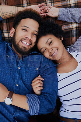 Buy stock photo Cropped shot of a happy young couple lying on a picnic blanket