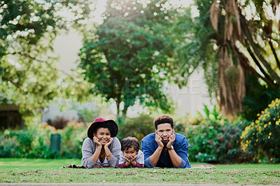 Buy stock photo Shot of a young family lying on the grass at a public park