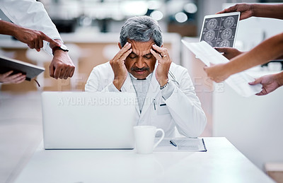 Buy stock photo Shot of a mature doctor looking stressed out in a demanding work environment