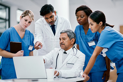 Buy stock photo Shot of a group of medical practitioners working together on a laptop in a hospital