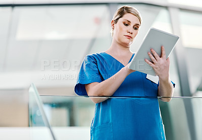 Buy stock photo Shot of a young nurse working on a digital tablet in a hospital