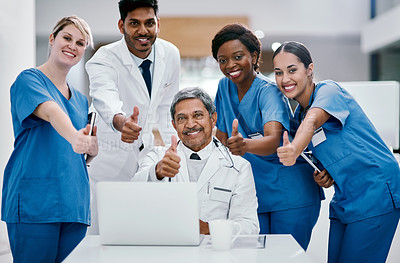 Buy stock photo Portrait of a group of medical practitioners showing thumbs up while working together on a laptop in a hospital