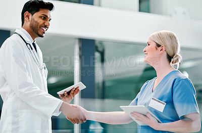 Buy stock photo Shot of two medical practitioners shaking hands in a hospital