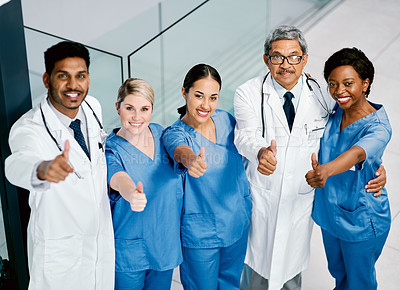 Buy stock photo Portrait of a group of medical practitioners showing thumbs in a hospital