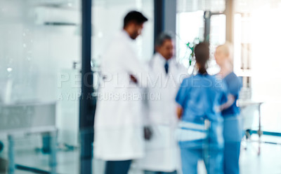 Buy stock photo Defocused shot of a group of medical practitioners working in a hospital