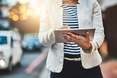 Buy stock photo Closeup shot of an unrecognizable businesswoman using a digital tablet in the city