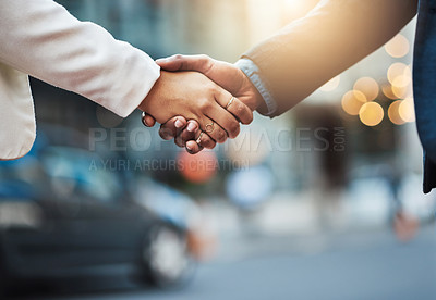 Buy stock photo Closeup shot of two unrecognizable businesspeople shaking hands in the city