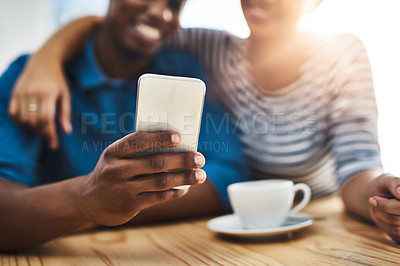 Buy stock photo Shot of a young man and woman using a mobile phone together on a date at a coffee shop