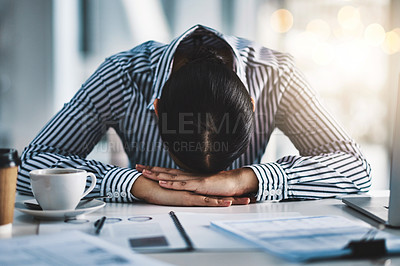 Buy stock photo Shot of a young businesswoman lying with her head down on a desk in an office
