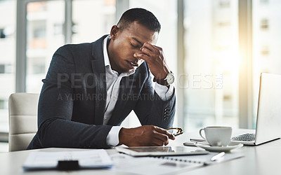 Buy stock photo Cropped shot of a young businessman suffering with a headache while working in his modern office