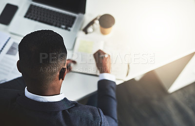 Buy stock photo High angle shot of an unrecognizable young businessman taking notes while working in his modern office