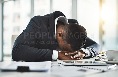 Buy stock photo Cropped shot of a young businessman sleeping at his desk after a long and tiring day
