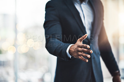 Buy stock photo Cropped shot of an unrecognizable young businessman offering his hand while standing in his modern office