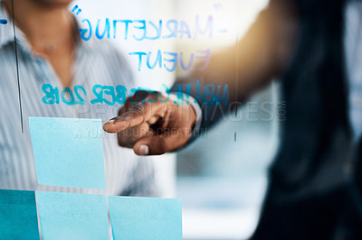 Buy stock photo Closeup shot of two unrecognizable businesspeople brainstorming with notes on a glass wall in an office