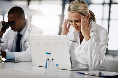Buy stock photo Cropped shot of a mature female scientist suffering with a headache while working in her research lab
