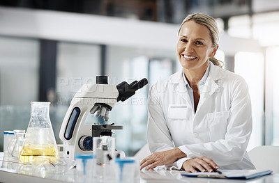 Buy stock photo Cropped portrait of an attractive mature female scientist using a microscope while doing research in her lab