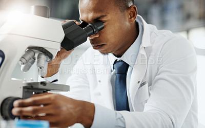 Buy stock photo Cropped portrait of a handsome young male scientist using a microscope while doing research in his lab