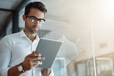 Buy stock photo Cropped shot of a handsome young businessman working on his digital tablet while standing in the office
