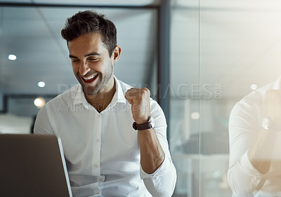 Buy stock photo Cropped shot of a handsome young businessman cheering while working on his laptop in the office