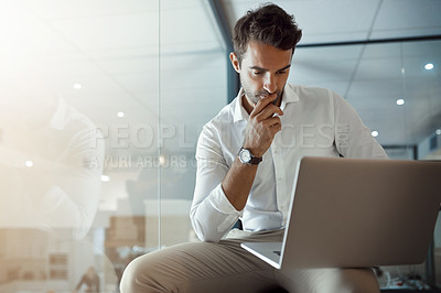 Buy stock photo Cropped shot of a handsome young businessman looking thoughtful while working on his laptop in the office