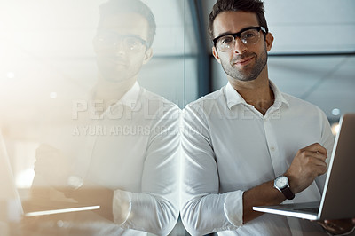 Buy stock photo Cropped portrait of a handsome young businessman working on his laptop while standing in the office