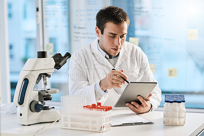 Buy stock photo Cropped shot of a handsome young male scientist working on a tablet in his lab