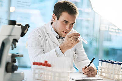 Buy stock photo Cropped shot of a handsome young male scientist checking samples in his lab