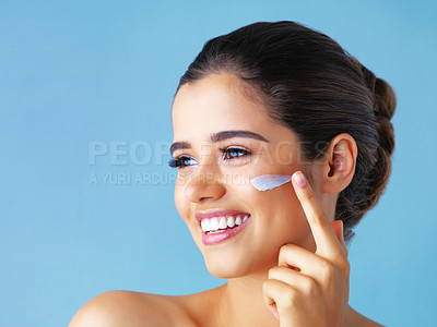 Buy stock photo Studio shot of a beautiful young woman applying lotion to her face against a blue background