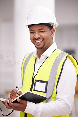 Buy stock photo Shot of a building contractor writing in a notebook